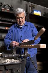Germany, Bavaria, Josefsthal, blacksmith working at bench vice in historic blacksmith's shop