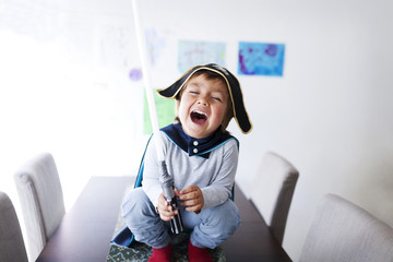 Portrait of laughing little boy dressed up as a pirate