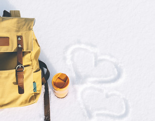 Orange backpack with leather elements and yellow thermos of hot tea or coffee on a background of white pure snow in winter mountains with empty space for text