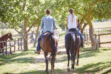 Young couple riding at paddock