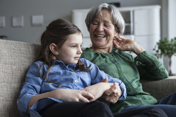 Grandmother and her granddaughter sitting together on the couch at home