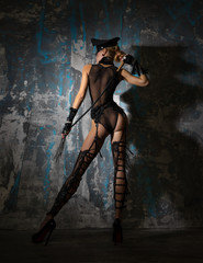 Girl in a cap, in beautiful lingerie with a whip stands near the wall.