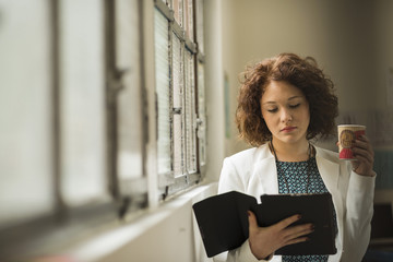 Young businesswoman reading personal organizer