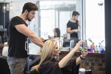 Woman in hair salon checking hairstyle in mirror an taking selfie