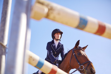 Young woman on horse approaching obstacle on course
