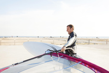 Smiling man at the coast holding surfboard