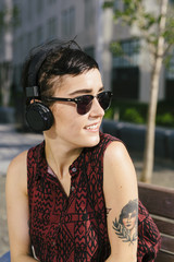 Portrait of tattooed young woman with headphones and sunglasses