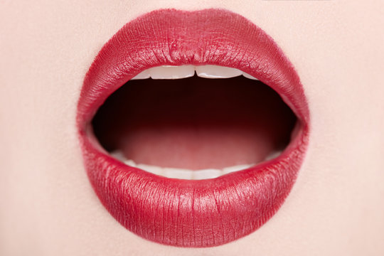 Close-up of open mouth woman with beautiful red lips