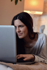 woman looking at her laptop in bed