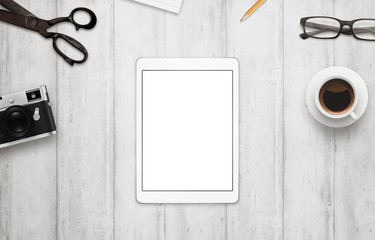 Tablet with isolated white screen for mockup. Work desk with camera, glasses, coffee, notepad and pencil beside on wooden table. Top view.