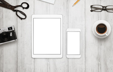 Tablet and smart phone with isolated white screen for mockup. Work desk with camera, glasses, coffee, notepad and pencil beside on wooden table. Top view for responsive app presentation.