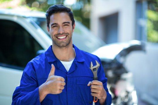 Portrait of happy mechanic with wrench showing thumbs up