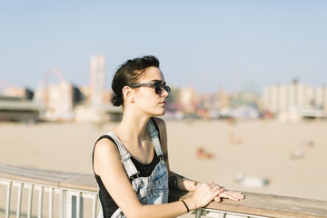 USA, New York, Coney Island, young woman relaxing at beach promenade