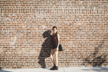 Portrait of young woman leaning against brick wall