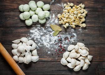 Different types of meat dumplings - russian pelmeni on wooden background