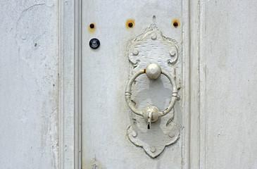 Old door knocker in closed door