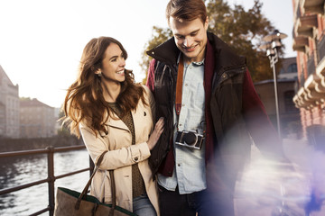 Germany, Berlin, happy young couple walking along River Spree