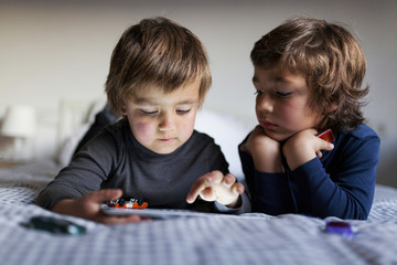 Two little boys lying on bed playing with digital tablet