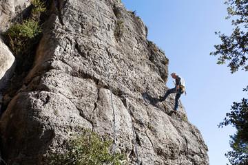 Spain, Tarragona, Siurana, climber climbing a stone wall