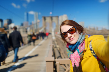 Beautiful young woman taking a selfie with her smartphone on Brooklyn Bridge, New York