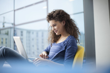 Smiling young woman using laptop at the  window
