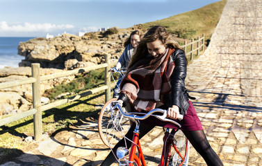 Two happy young women riding bicycle along a path