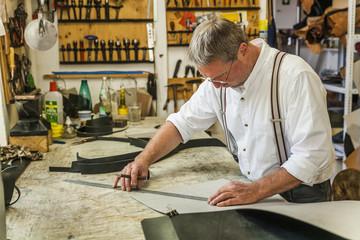 Saddler preparing stencil for rucksack