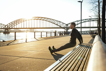 Germany, Cologne, Young man doing push ups on bench