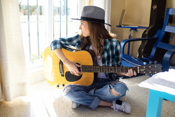 Young woman sitting on the floor playing guitar
