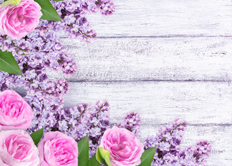Lilac flowers with roses on shabby wooden planks