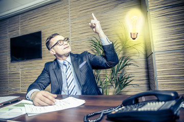the businessman raised a finger as a sign of getting ideas, light turn on