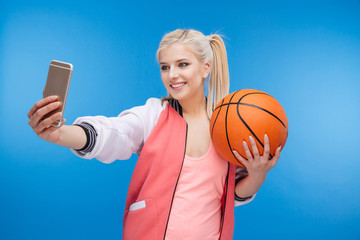 Female teenager holding basketball ball and making selfie photo