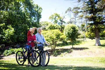 Senior couple walking with bicycle in park