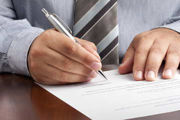 Closeup of businessman or salesman hand signing contract with silver ballpoint