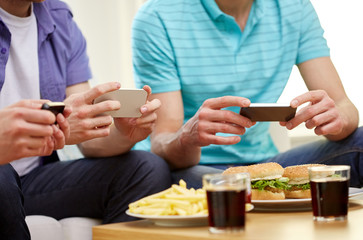 close up of friends with smartphone picturing food