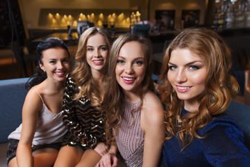 happy smiling women taking selfie at night club