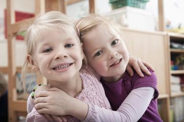 Portrait of two little girls, best friends, side by side in kindergarten