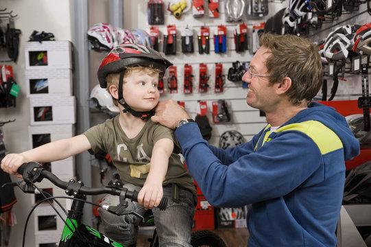 Germany, Bavaria, Boy with bicycle helmet in bike shop