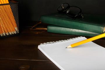 desktop with a notebook and pencil closeup