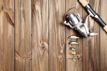 the fishing rod stand on the wooden background.