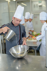 Chef pouring into stainless steel bowl