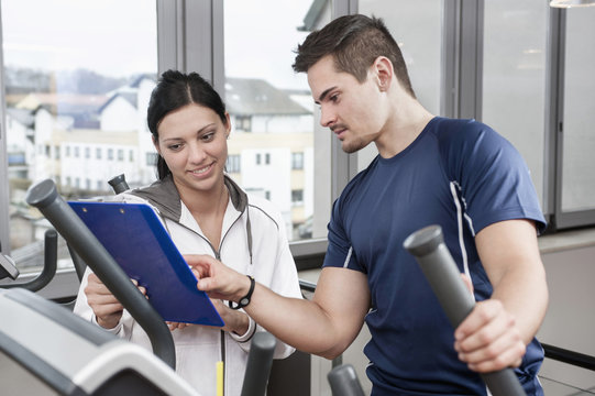 Young woman and man in gym