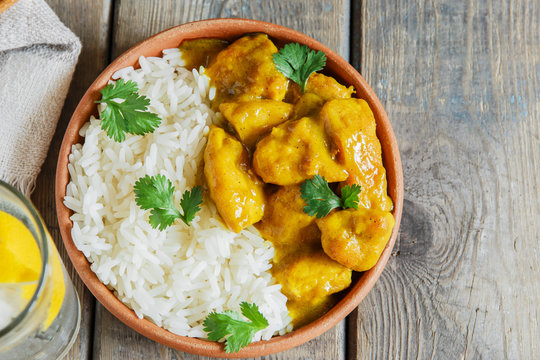 chicken curry with rice on a wooden surface