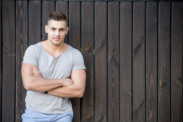 Portrait of young man in front of wooden wall