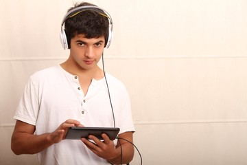 A young, latin man with a Tablet PC and headphones.