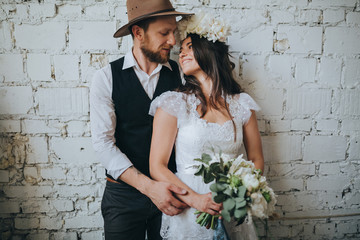 girl with a wreath of white flowers on the head in a white wedding dress and a bearded man in a...