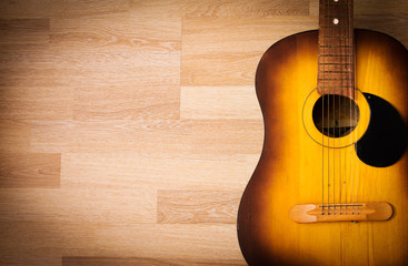 Acoustic guitar resting against a blank wooden background