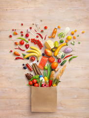 Healthy products in package. Studio photography of different fruits and vegetables on wooden background, top view. High resolution.