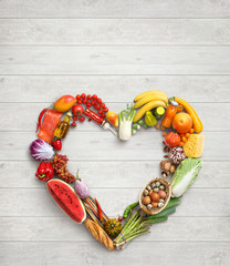 Heart symbol. Food photography of heart made from different vegetables on white wooden table. High resolution product.