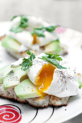 Poached egg with avocado on white bread.